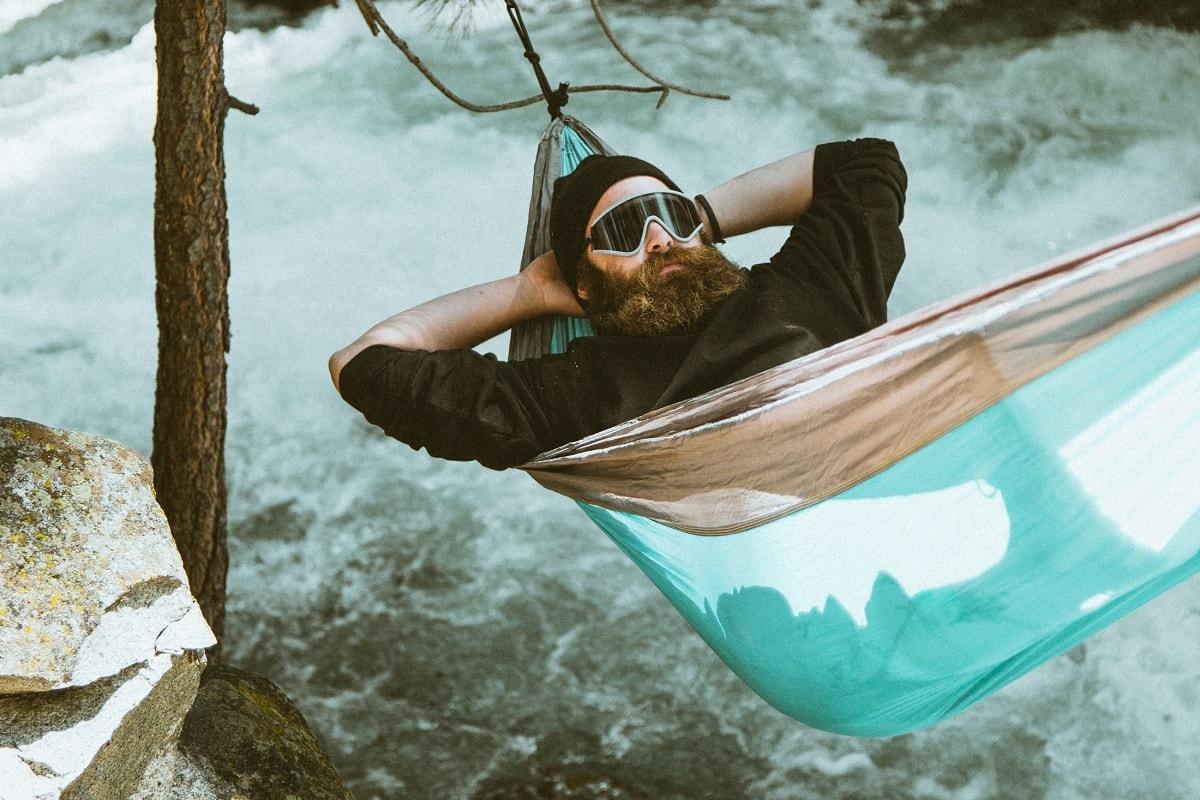 Ein Mann in einer Hängematte an einem Bergbach. (Foto: Dane Deaner, Unsplash.com)