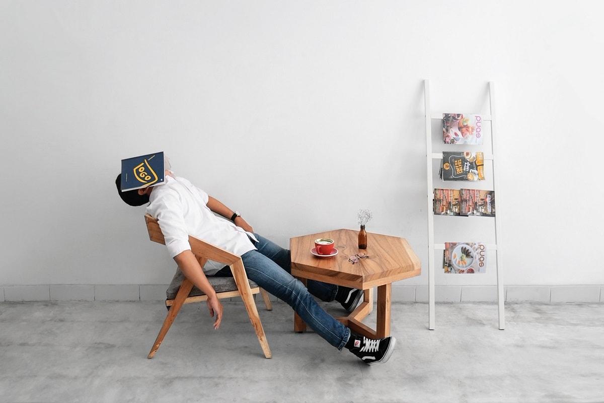 Ein Mann schläft und hat ein Buch vor dem Gesicht. (Foto: Hutomo-Abrianto, Unsplash.com)